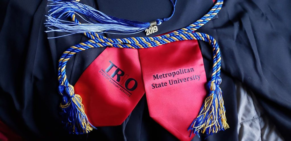 A red gratitude sash, blue and gold honors cord, blue and white 2019 tassel on a black graduation goan