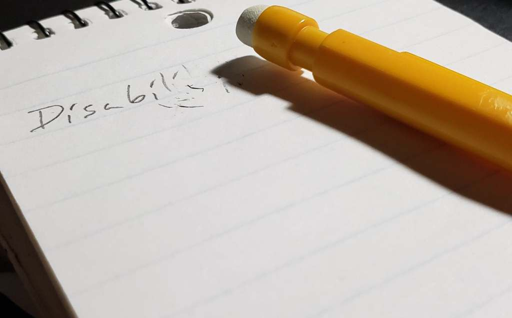 "A pad of paper with the last few letters of ""Disability"" erased. A yellow mechanical pencil lies on the paper."