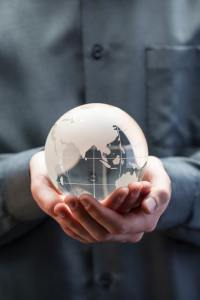 A person holding a small grey and white globe.
