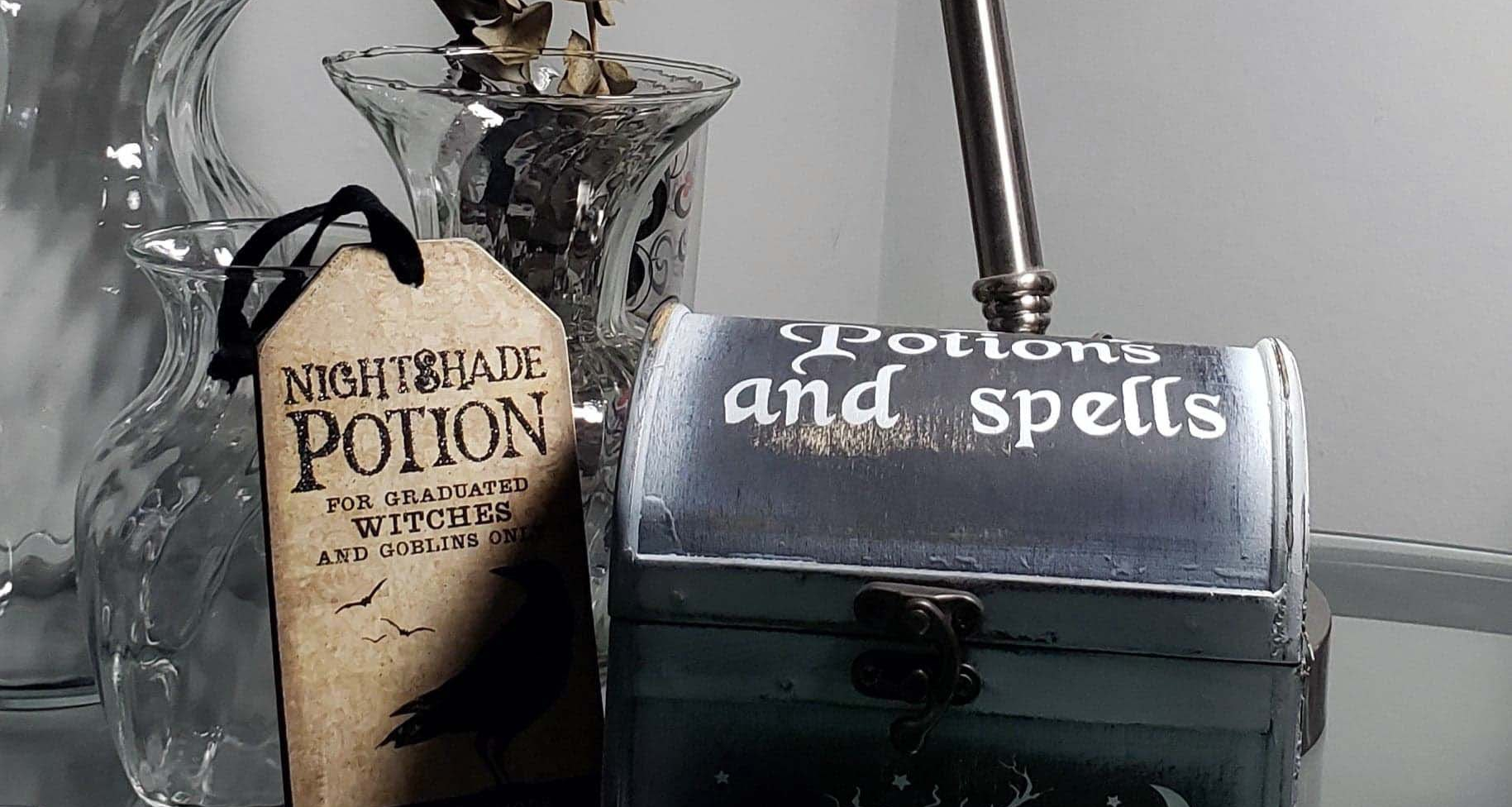 """Wellness corner of my desk - three glass vases of different sizes, one with dried eucalyptus in it, a wooden box that says """"Potions and Spells"""", and a tag saying """"Nightshade potion For graduated Witches and Goblins Only"""" with a picture of a bird on it."""